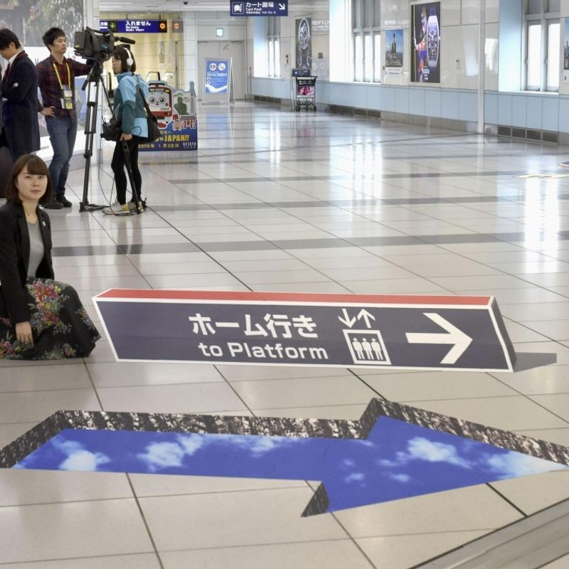 """Pop-up"" signs on floor help guide Tokyo airport passengers photo"