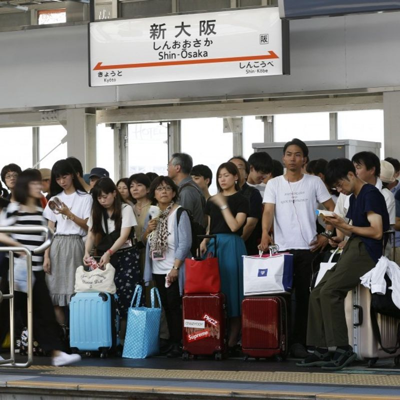 Travelers flood train stations, clog roads in holiday exodus photo