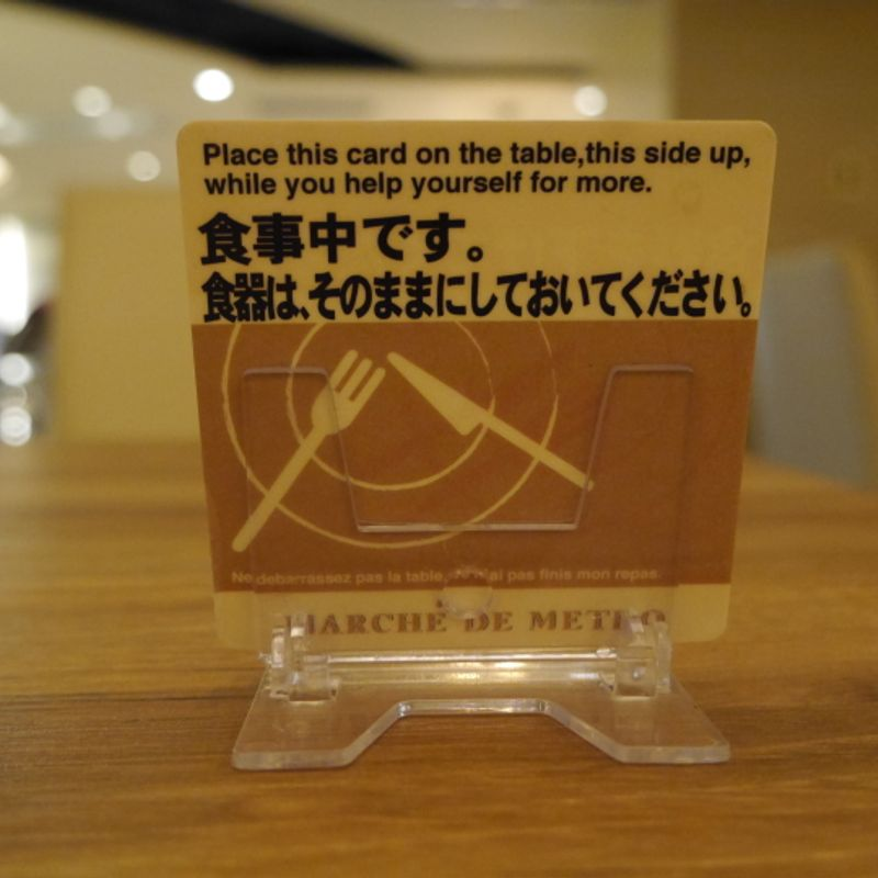 """Don't clean up"" card at a food court photo"